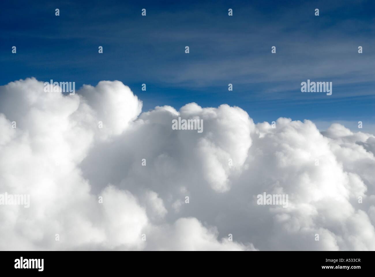 Puffy white cumulus nubi close up da aereo con cielo blu Immagini Stock