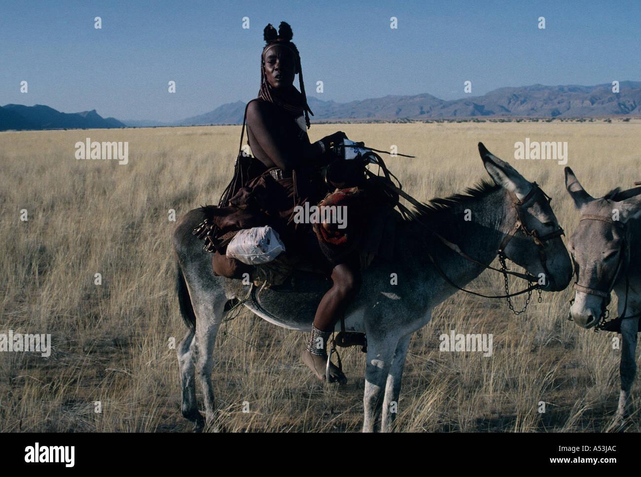 Himba donne nomadi nel tradizionale abbigliamento in pelle attraversando il Marienfluss su donkey in Kaokoland Namibia settentrionale Foto Stock