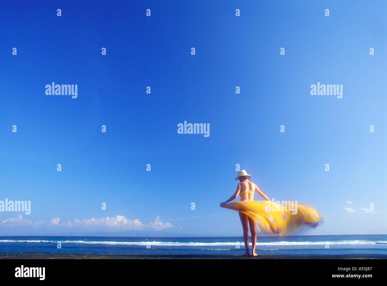 La donna in giallo sarong e oceano orizzonte in Bali Indonesia Modello rilasciato foto Immagini Stock
