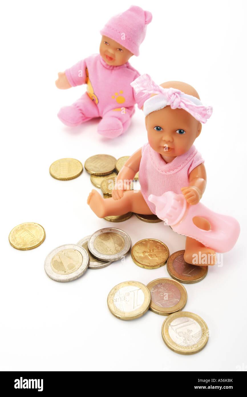 Due bambola seduta tra le monete metalliche in euro Immagini Stock