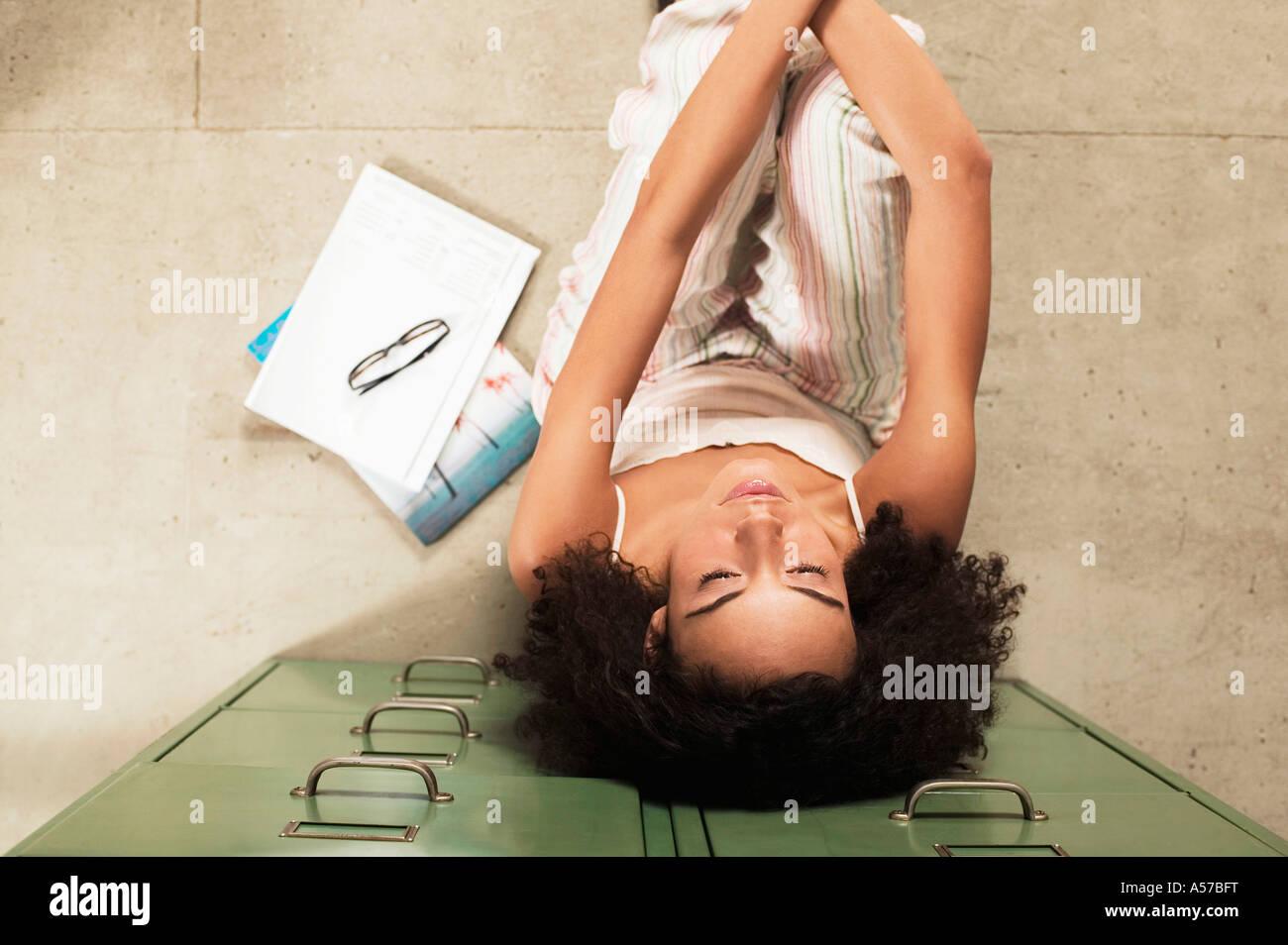 Giovane donna seduta sul pavimento a occhi chiusi, vista in elevazione Immagini Stock