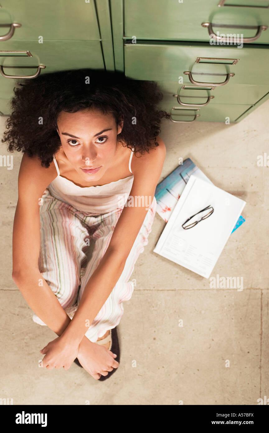 Giovane donna seduta sul pavimento, ritratto, vista aerea Immagini Stock