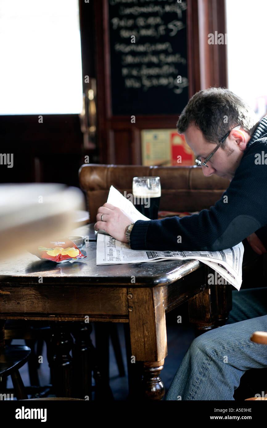 L uomo nel pub la lettura Immagini Stock