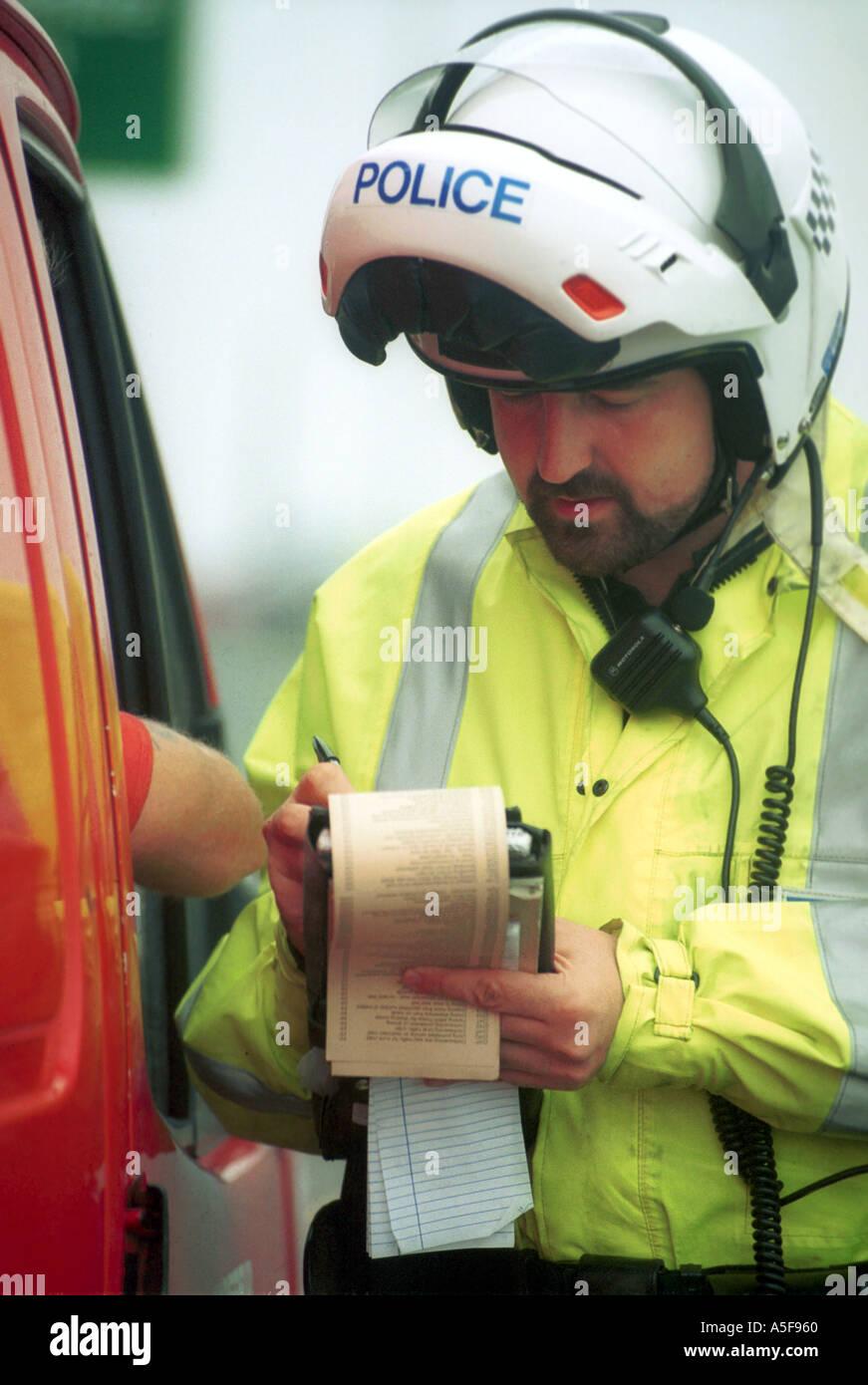 Polizia Stradale Officer emette un avviso di penalità per un automobilista Immagini Stock