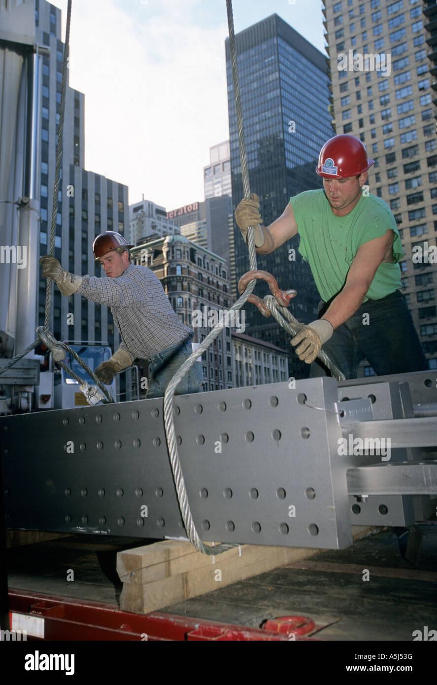 I lavoratori del ferro trave pronta per essere portato da una gru per Random House edificio a 1540 Broadway a New Immagini Stock
