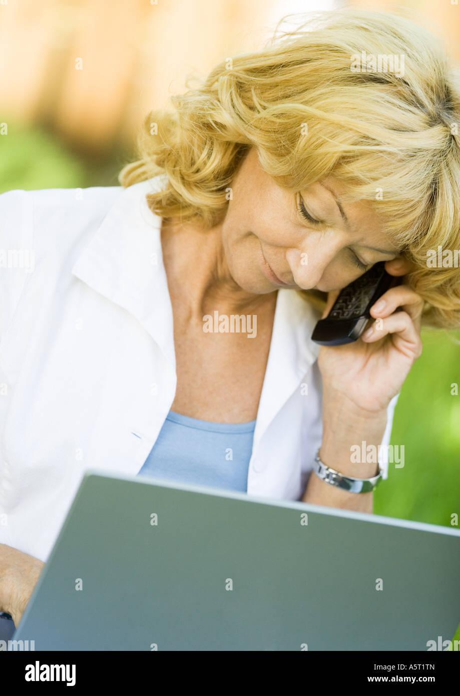 Senior donna utilizzando il telefono cellulare e il computer portatile Immagini Stock