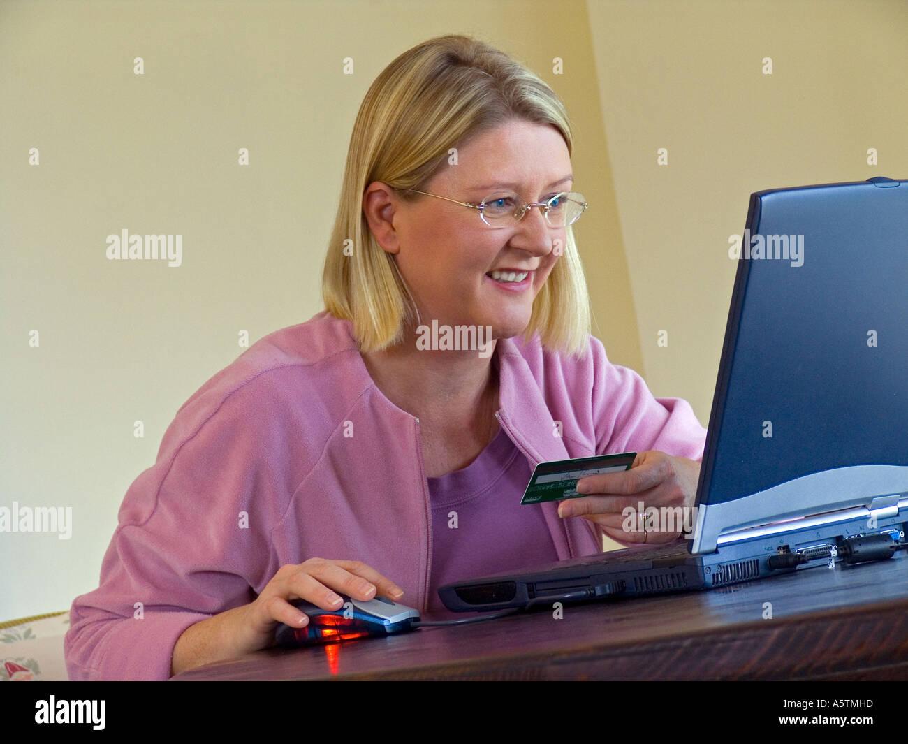 Sorridente fiducioso donna usa la sua carta di credito al negozio in linea con il suo computer portatile a casa Immagini Stock