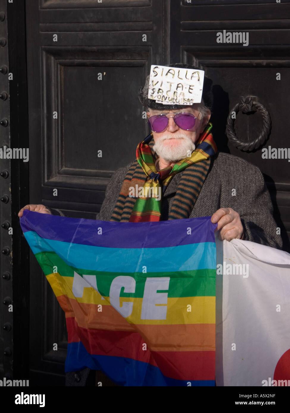 Il vecchio uomo in piedi una bandiera della pace a Roma Immagini Stock