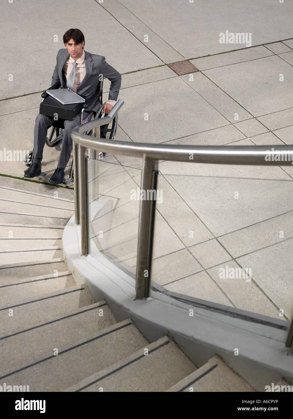 Uomo in sedia a rotelle guardando la scala Foto Stock
