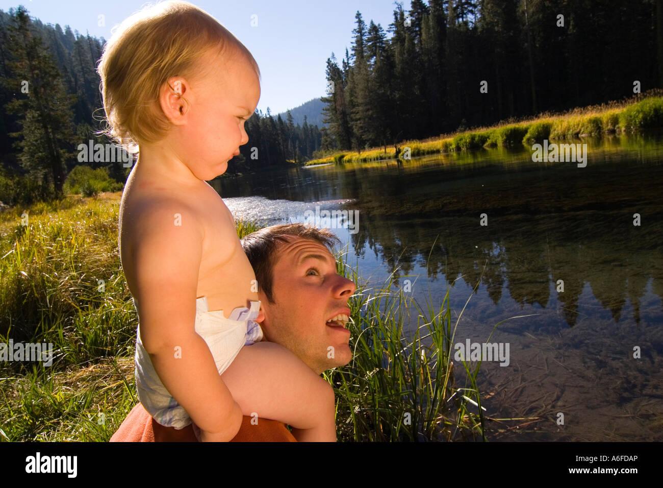 Un bambino seduto sul suo padri spalle dal fiume Truckee vicino a Tahoe City California Immagini Stock