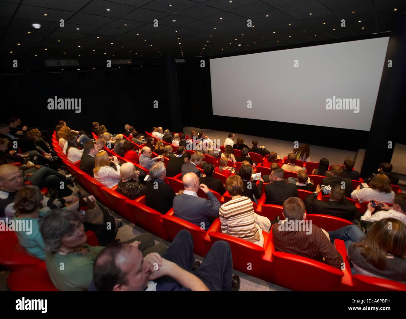 La gente a guardare uno schermo cinematografico in un teatro Immagini Stock