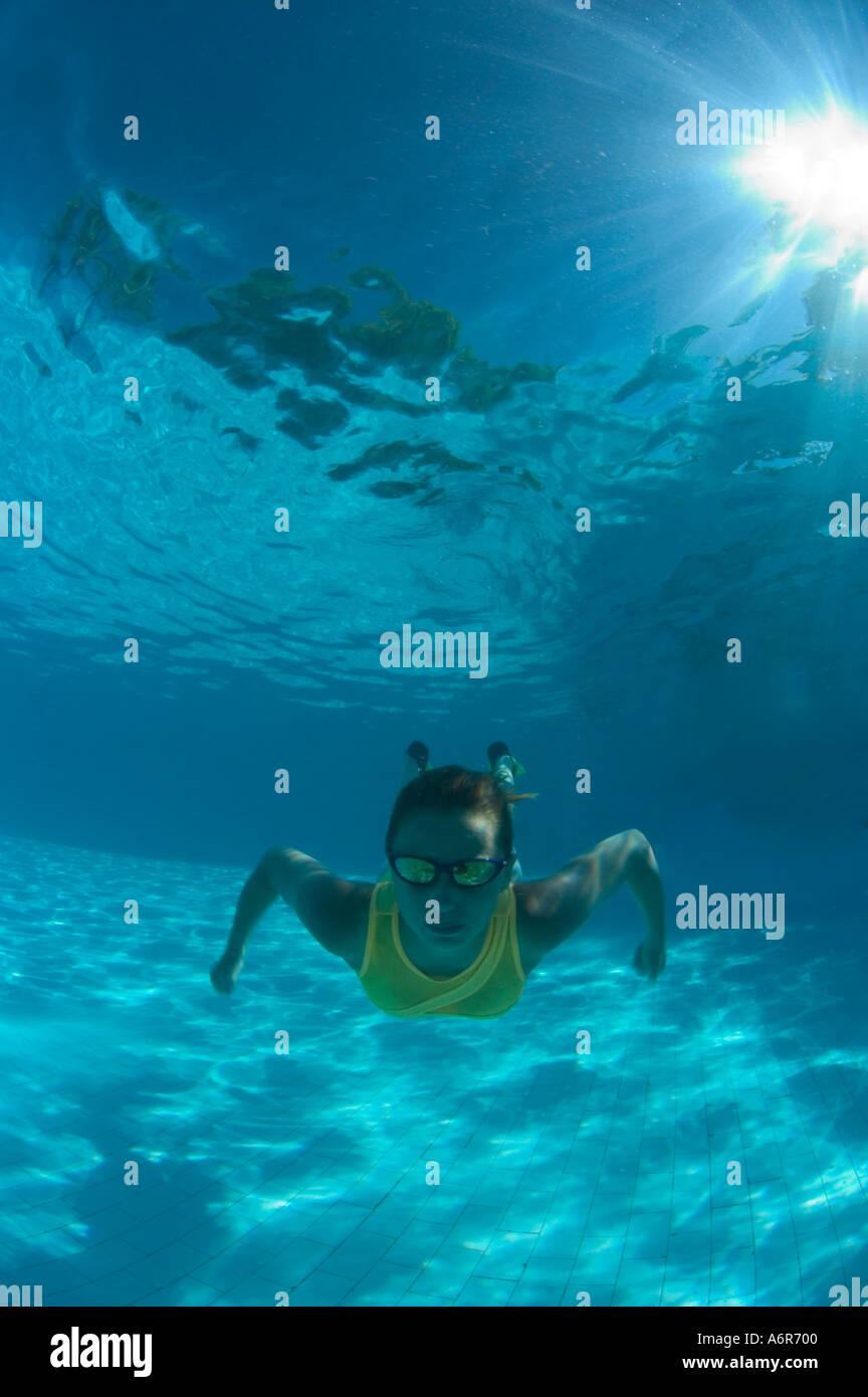 Ragazza di nuoto in piscina con il costume da bagno giallo le pinne e occhiali da sole Immagini Stock