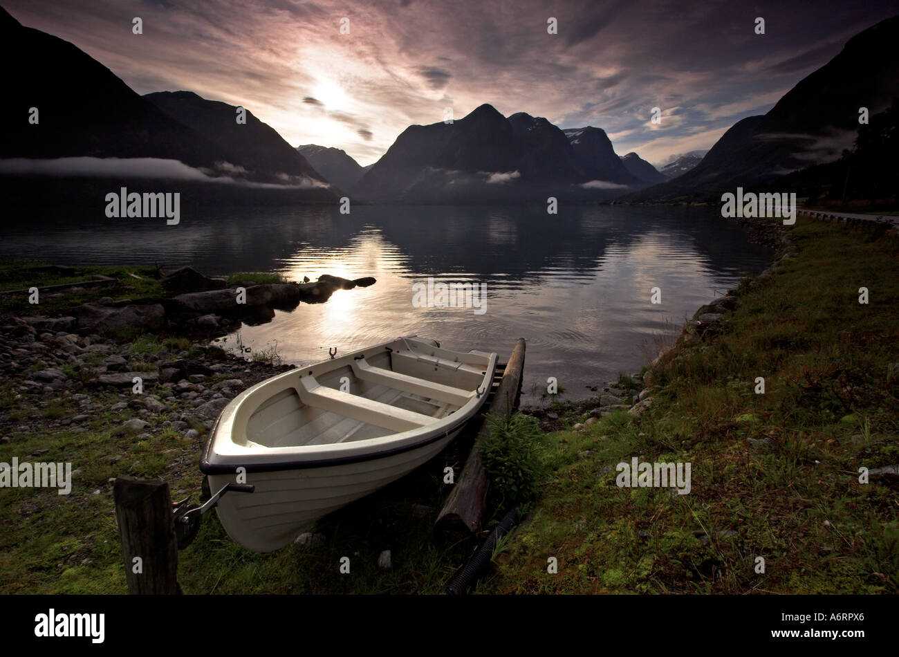 Una piccola barca ormeggiato sulle rive di un fiordo norvegese. Bassa wisps del cloud appendere sopra le acque ancora Immagini Stock