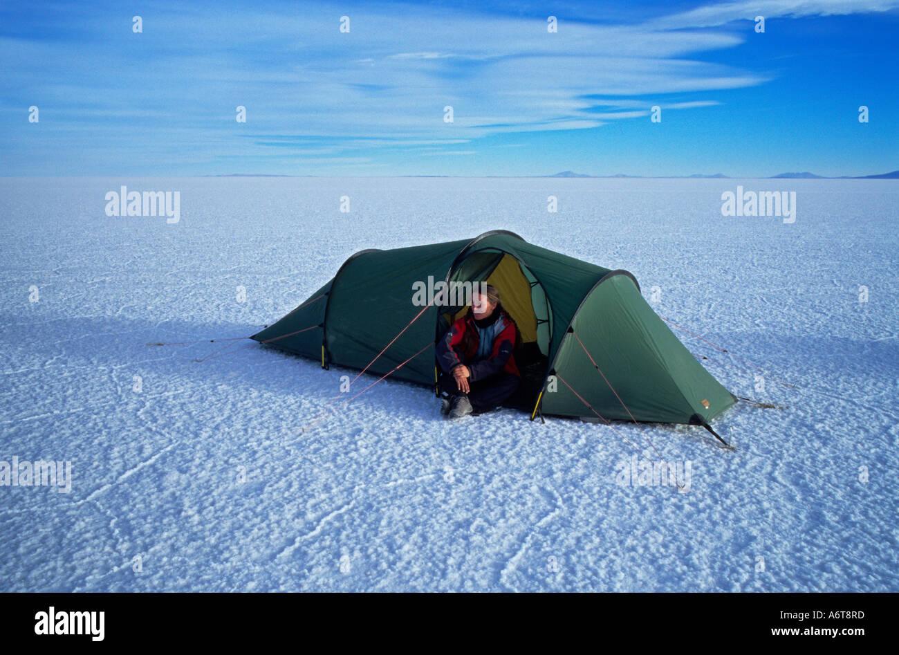 Donna seduta da sola in tenda con vasta distesa del Salar de Uyuni distesa di sale intorno a lei a 3800 metri di altitudine in Bolivia Immagini Stock