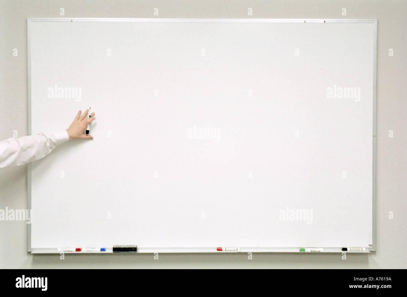 Imprenditore puntando alla lavagna mentre dando la presentazione Immagini Stock
