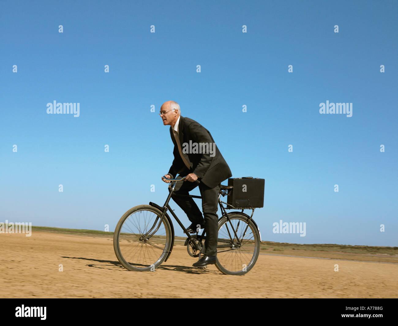 Imprenditore bicicletta equitazione nel deserto Immagini Stock
