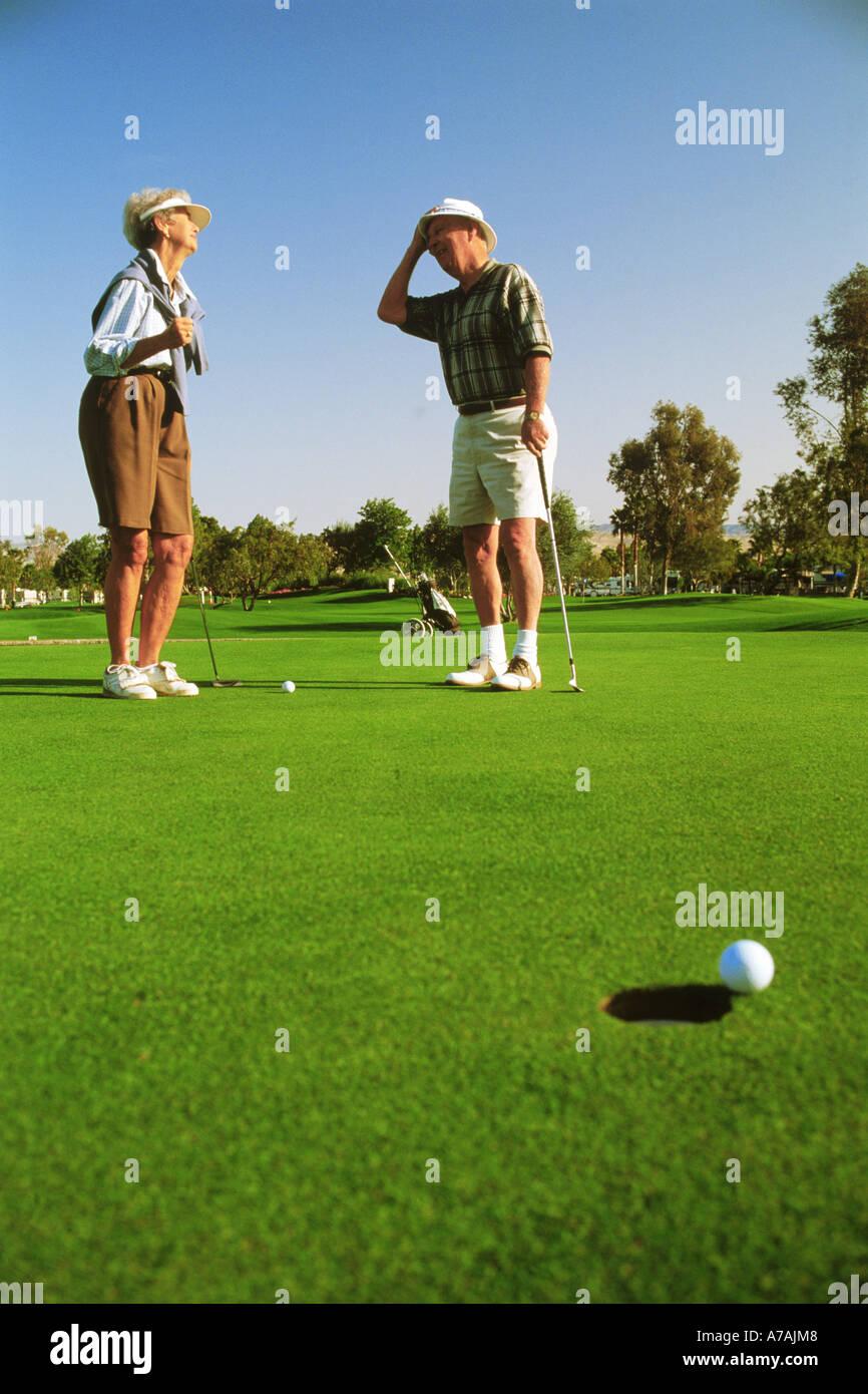 Matura nel loro 70s manca solo il putt mentre giocando a golf in Palm Springs, California Immagini Stock