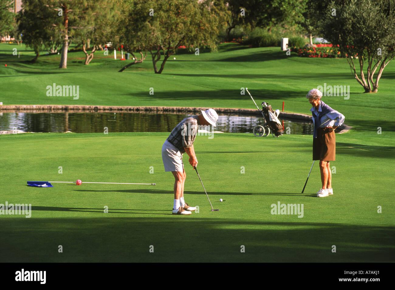 Coppia senior negli anni settanta per giocare a golf in Palm Springs, California Immagini Stock