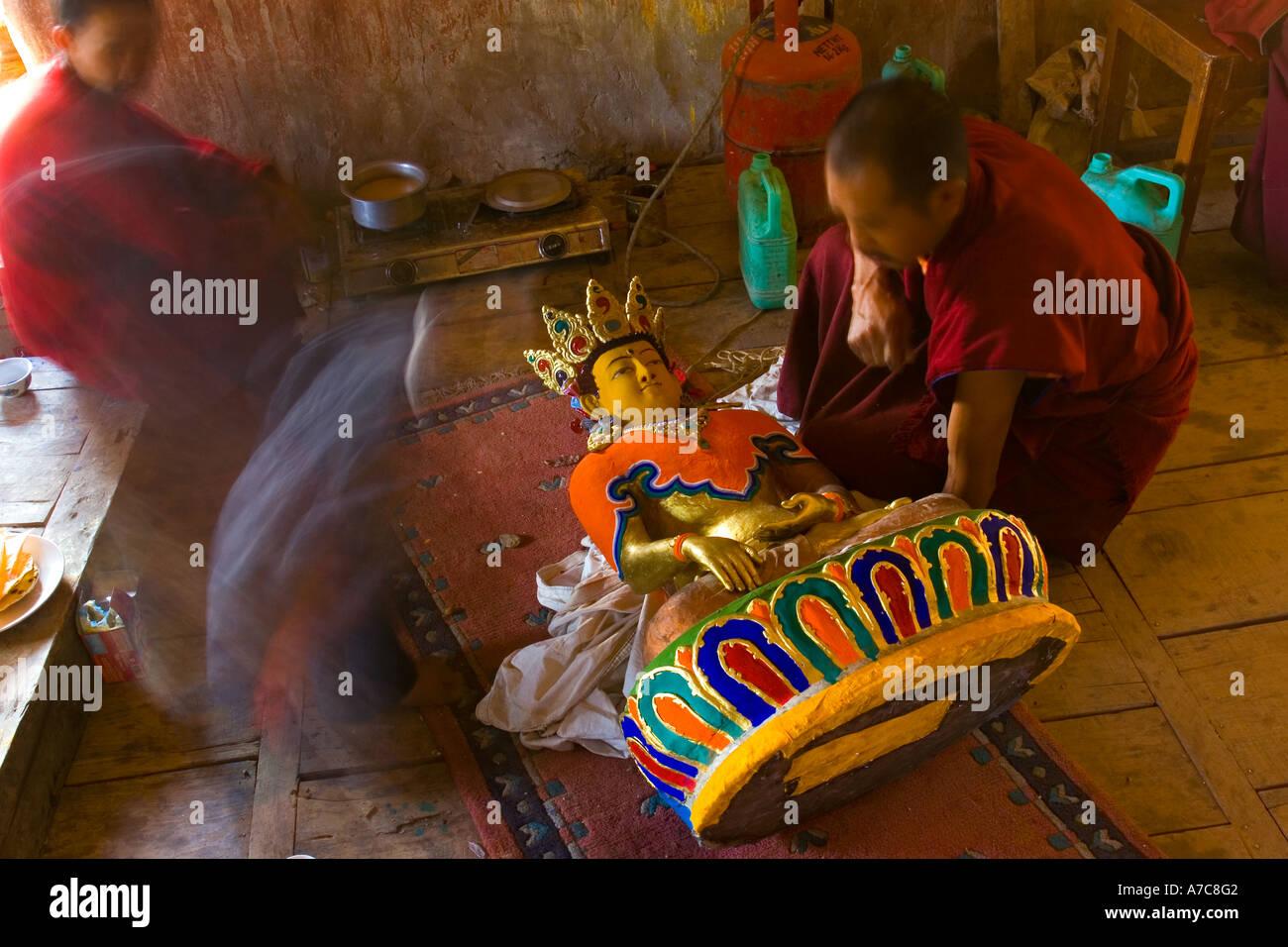 Giovane monaco verniciatura un Buddha all'interno del monastero di Thiksey Ladakh Himalaya indiano Foto Stock