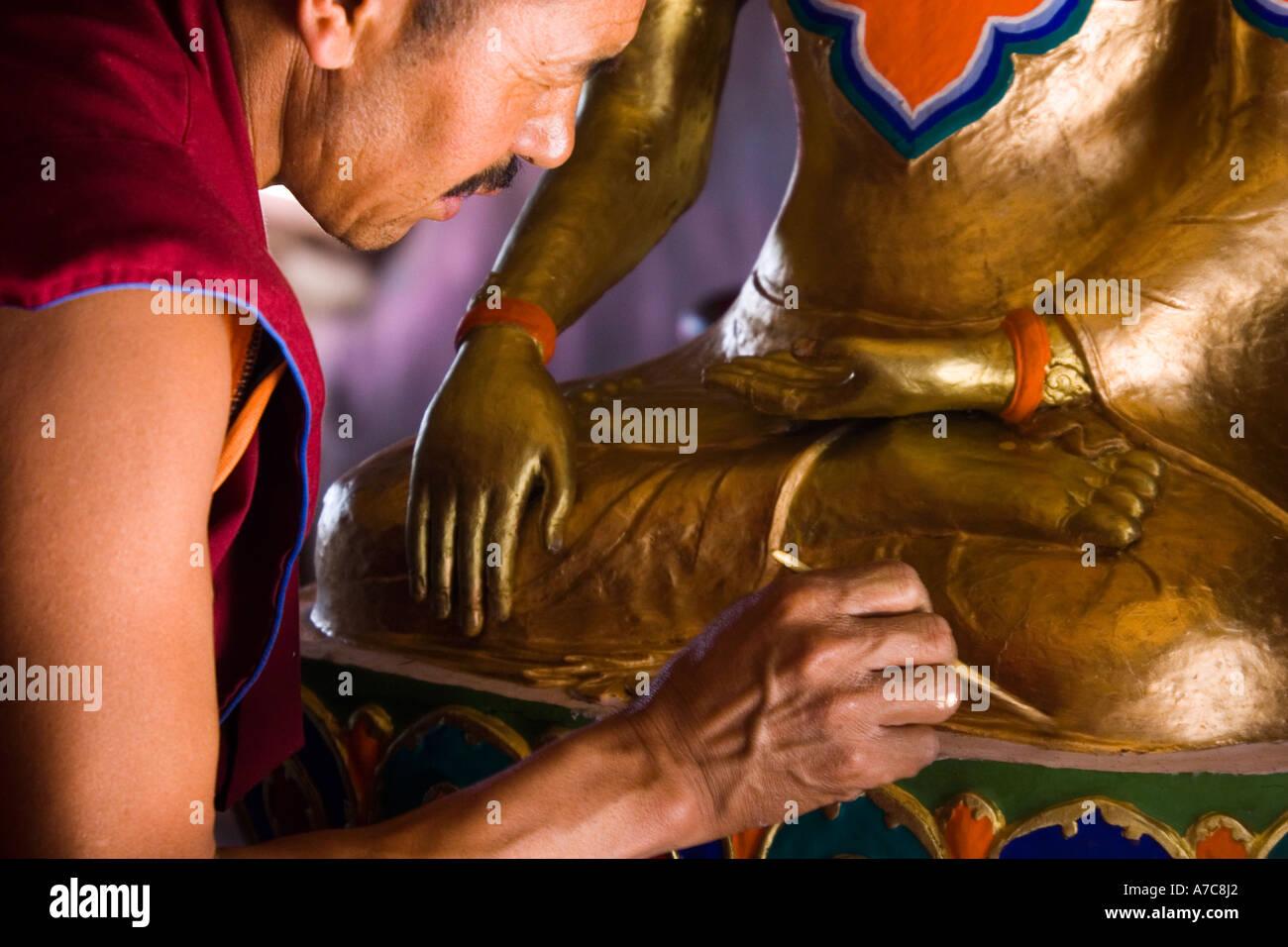 Giovane monaco verniciatura un Buddha all'interno del monastero di Thiksey Ladakh Himalaya indiano Immagini Stock