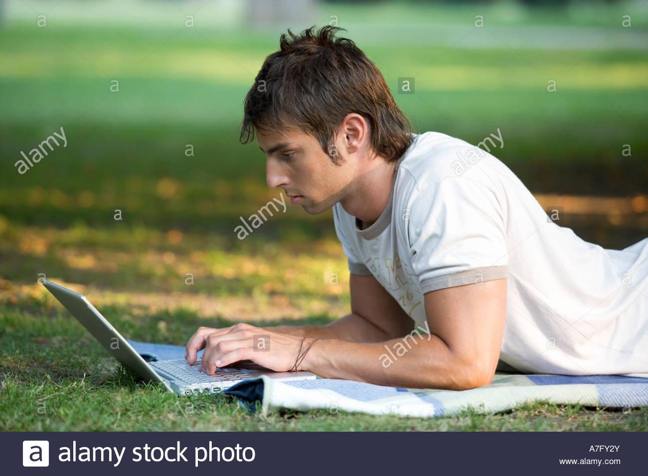 Un ragazzo adolescente lavora su un computer portatile in un parco Immagini Stock
