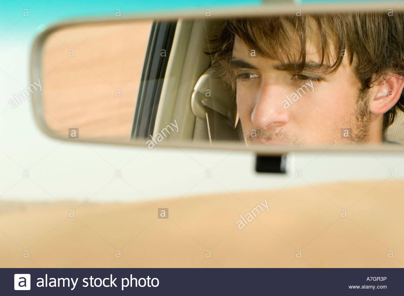 Un giovane di riflessione in uno specchio retrovisore Immagini Stock