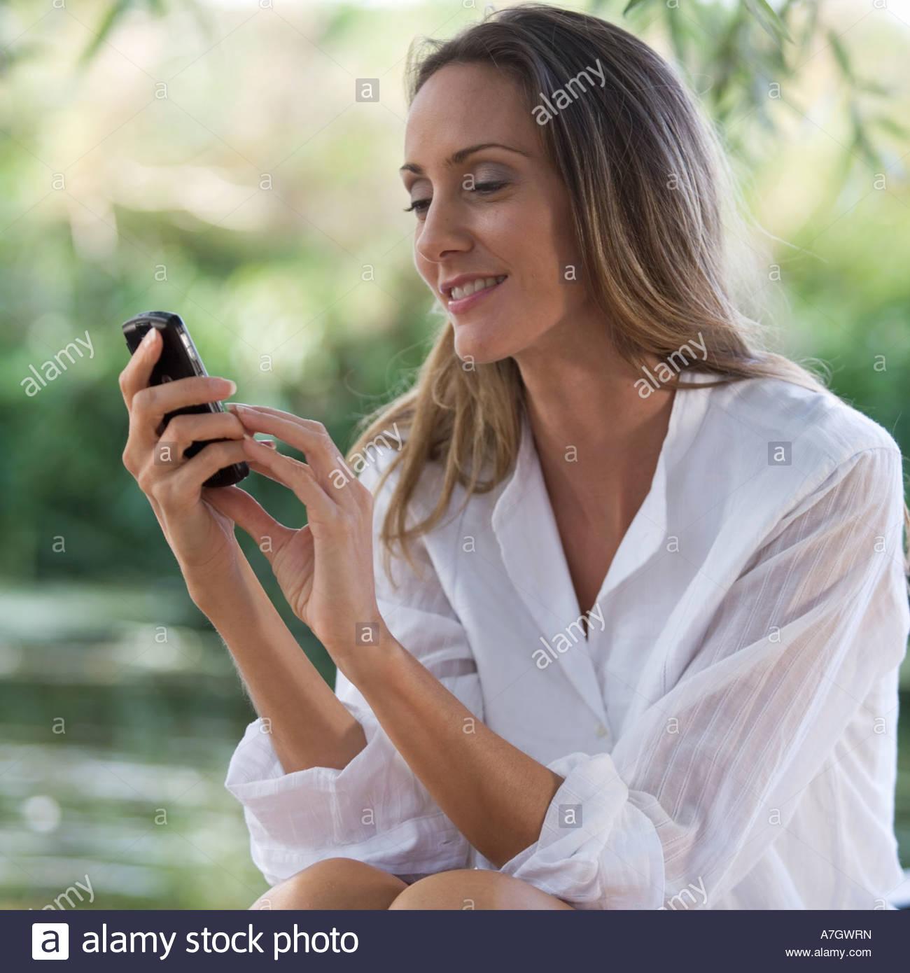 Giovane donna utilizzando un telefono cellulare Immagini Stock