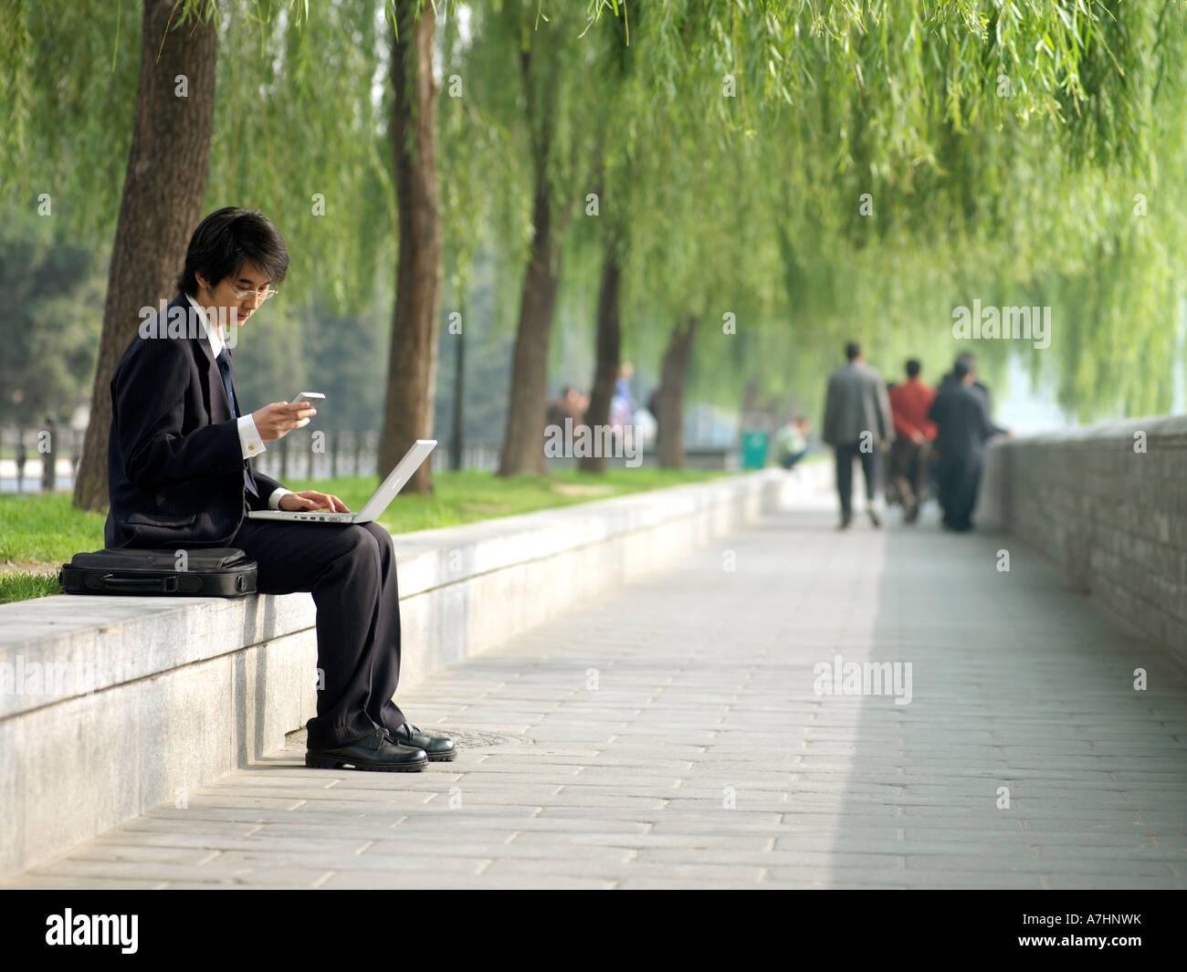 Un giovane cinese business man in una tuta controllare la sua posta elettronica sul suo computer portatile Immagini Stock