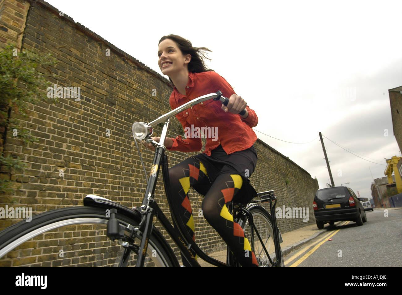 Una ragazza accelerando su un vecchio modello di ciclo su una strada con un muro di mattoni di fianco ed una macchina parcheggiata in background. Immagini Stock