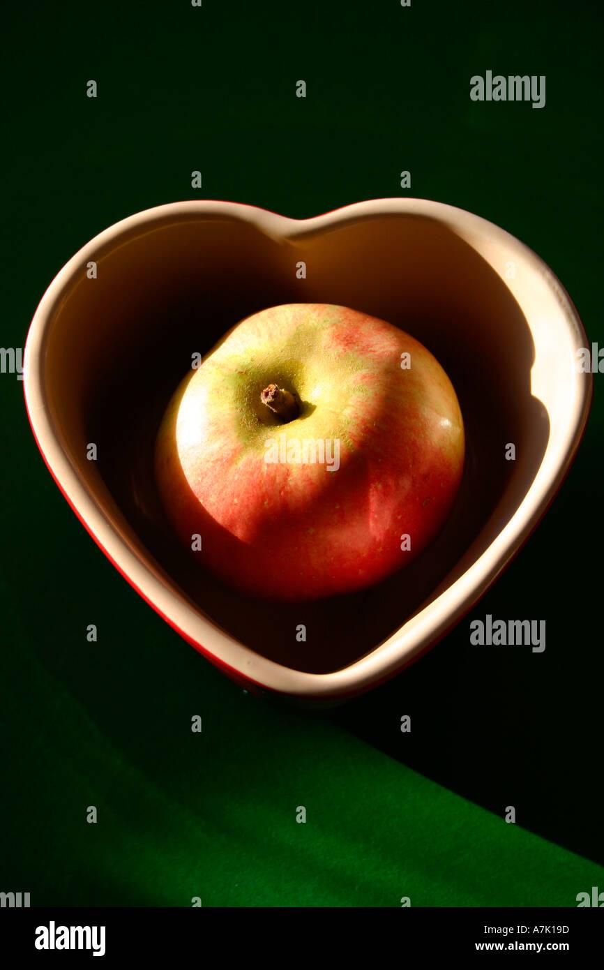Rosy Apple In Una Forma Di Cuore Piatto Su Uno Sfondo Verde Foto