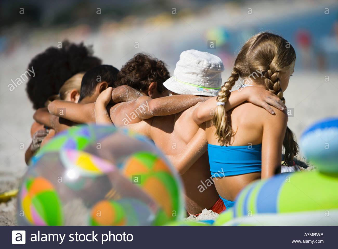 Bambini 4 9 seduto in linea sulla spiaggia vista posteriore di messa a fuoco del differenziale Immagini Stock