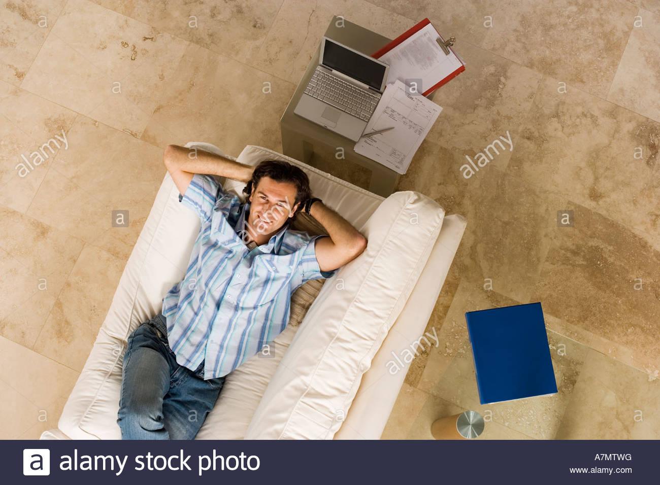 Tavolo Dietro Al Divano : Uomo disteso su un divano accanto al computer portatile sul tavolo