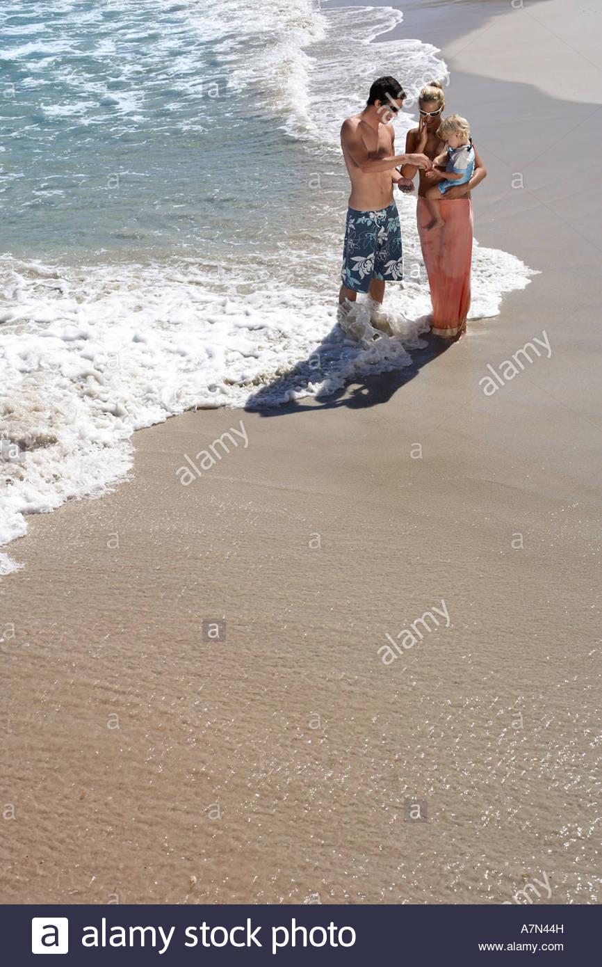 Famiglia permanente sulla spiaggia di surf donna che trasportano figlia 2 4 vista in elevazione Foto Stock