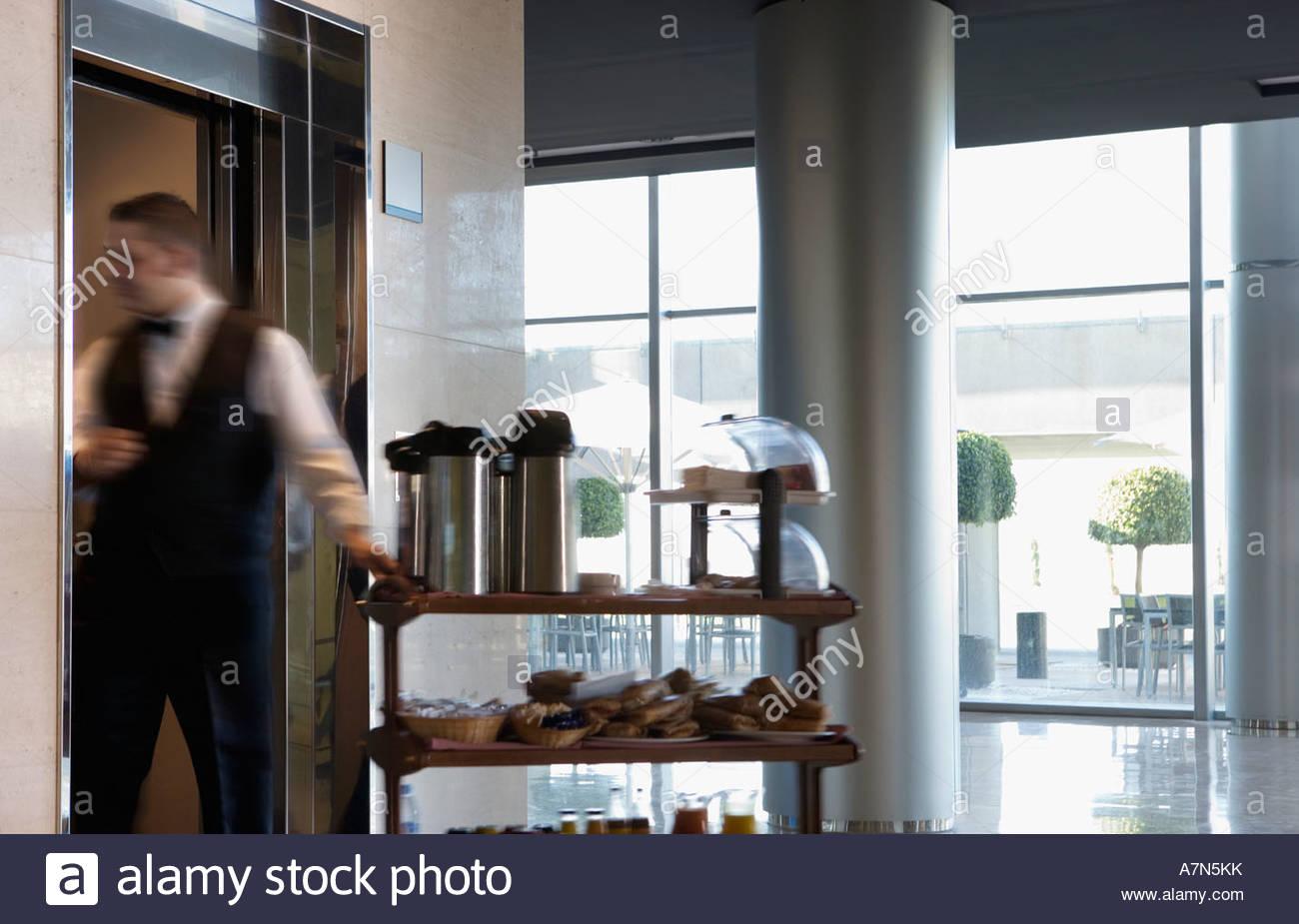 Cameriere entrando in ascensore nella lobby e tirando il cibo e le bevande carrello vista laterale Immagini Stock