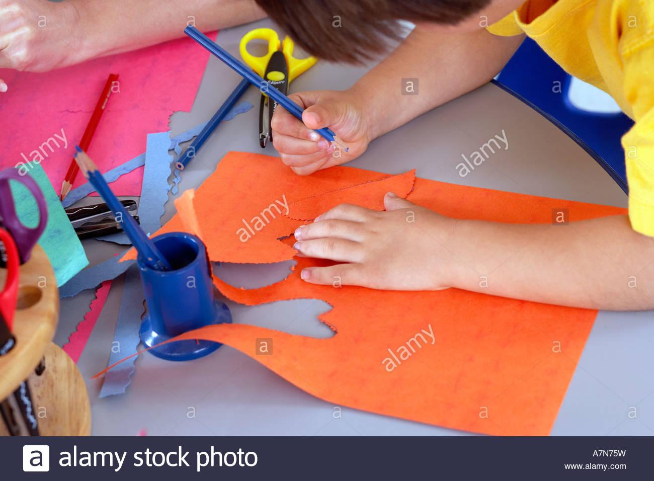 Boy 4 6 forme di taglio al di fuori della carta arancione al banco in aula vista laterale vicino fino Immagini Stock