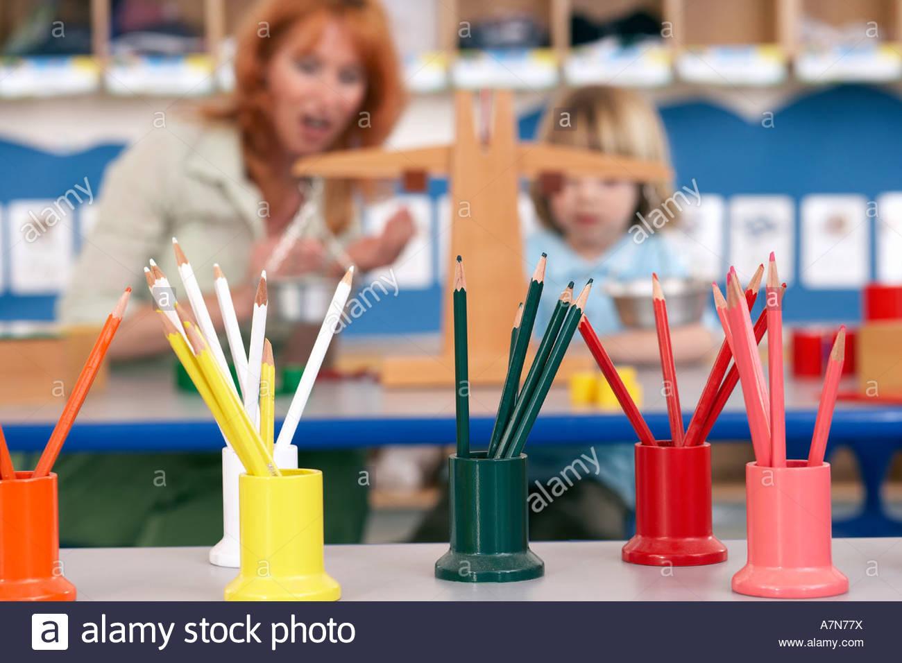 Boy 4 6 e il maestro utilizzando la scala di peso in aula concentrarsi sulle matite colorate in primo piano Immagini Stock