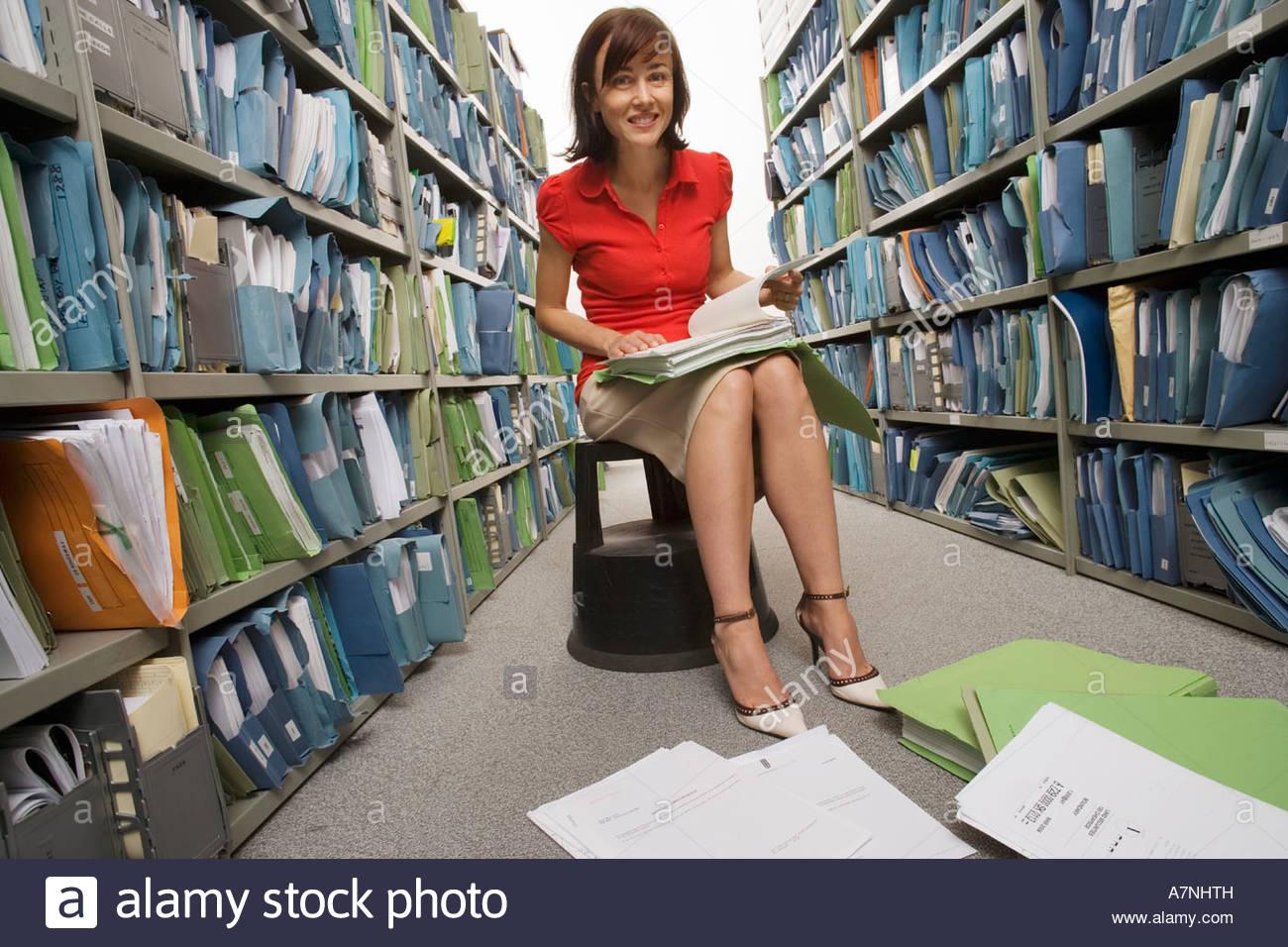 Donna che indossa gonna tacchi alti e parte superiore rossa seduta