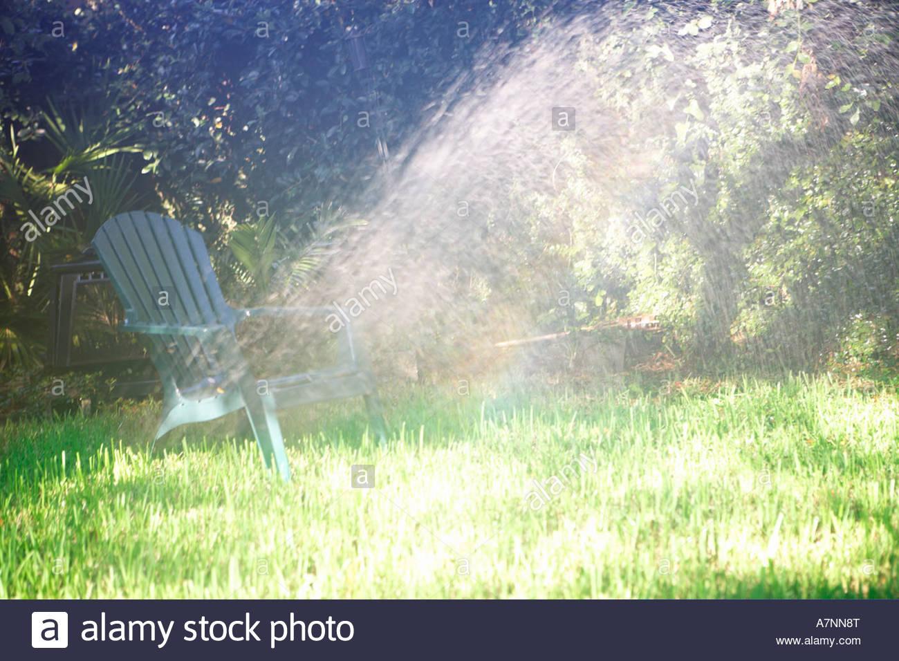 Sedia all'aperto sul giardino prato sotto la luce diretta del sole Immagini Stock