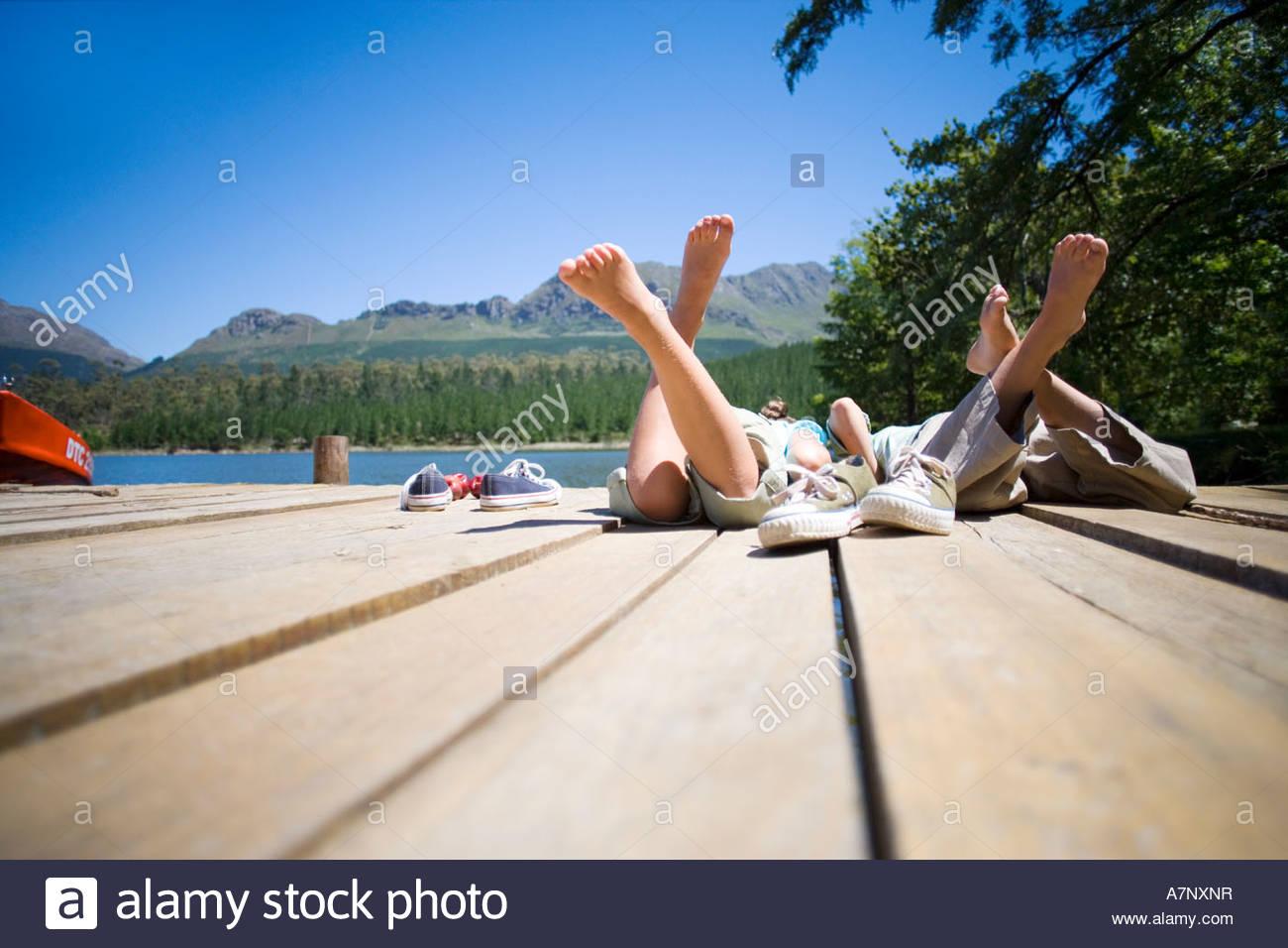 Un ragazzo e una ragazza 7 10 affiancati sul lago jetty scarpe fuori vista posteriore a livello della superficie Immagini Stock