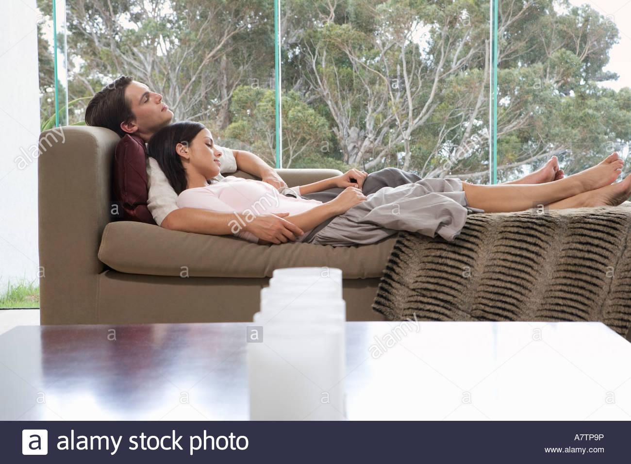 Una giovane coppia posa su un divano Immagini Stock