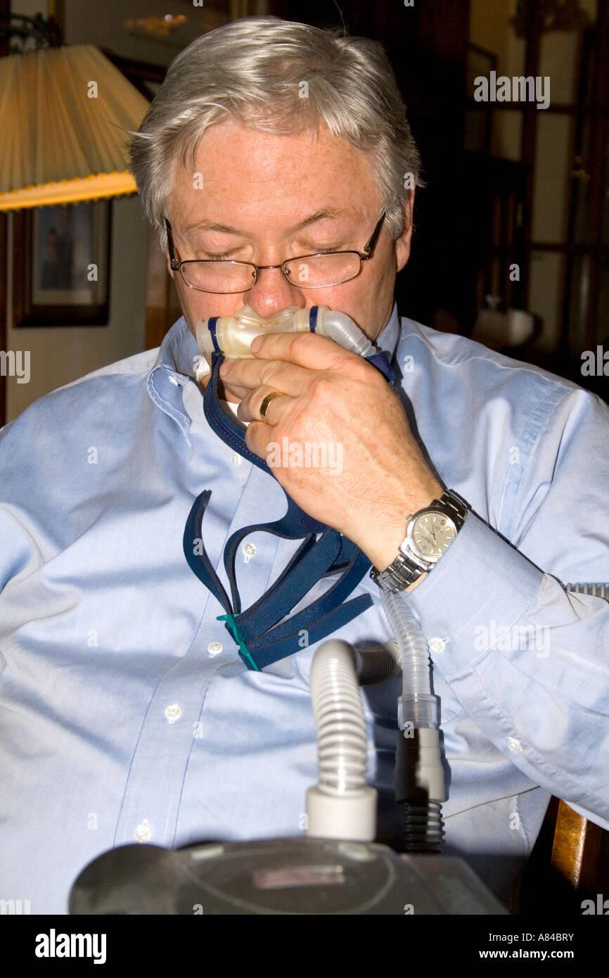 L'uomo 59 anni test di una apnea respirazione CPAP macchina usata da persone con problemi di sonno. 'St Immagini Stock