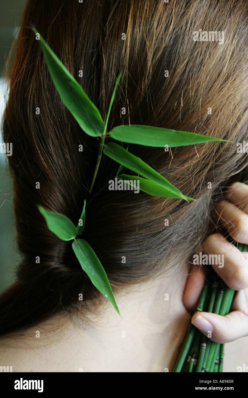 Retro di una testa di donna con foglie di bambù in her hair Immagini Stock