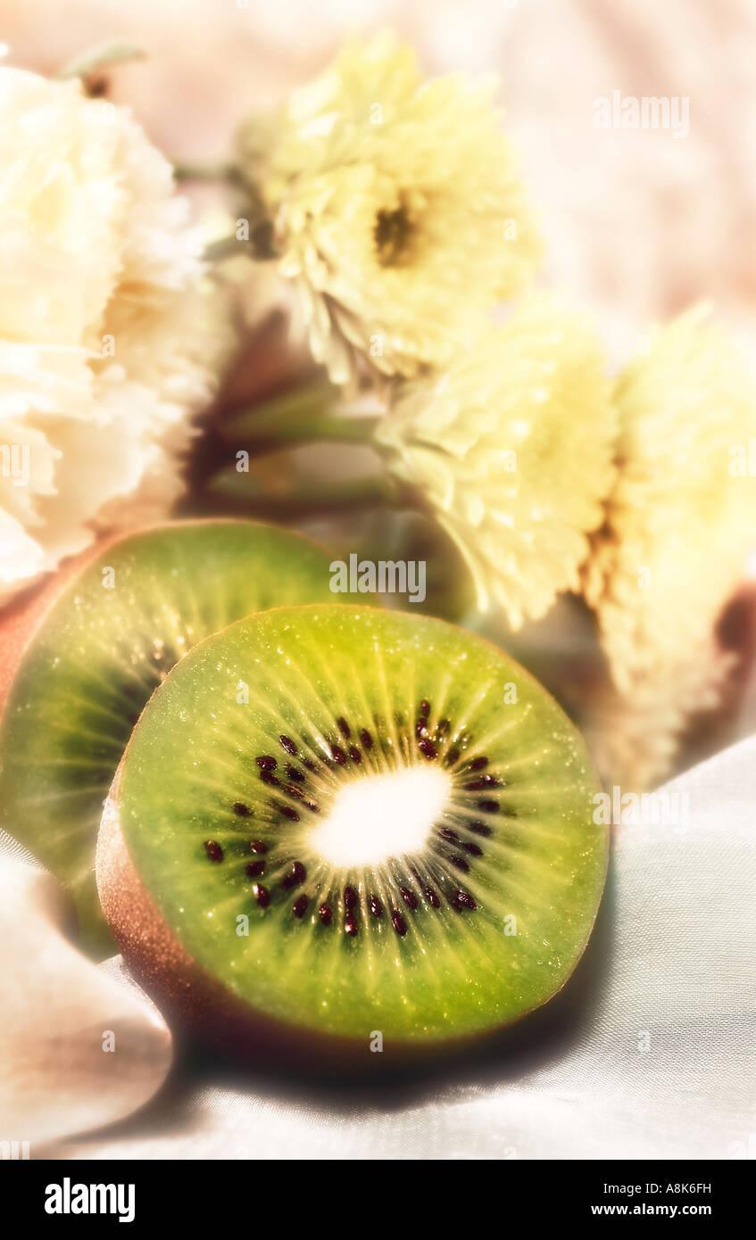 Ancora la vita di Kiwi tagliato a metà con sottofondo di fiori bianchi Immagini Stock