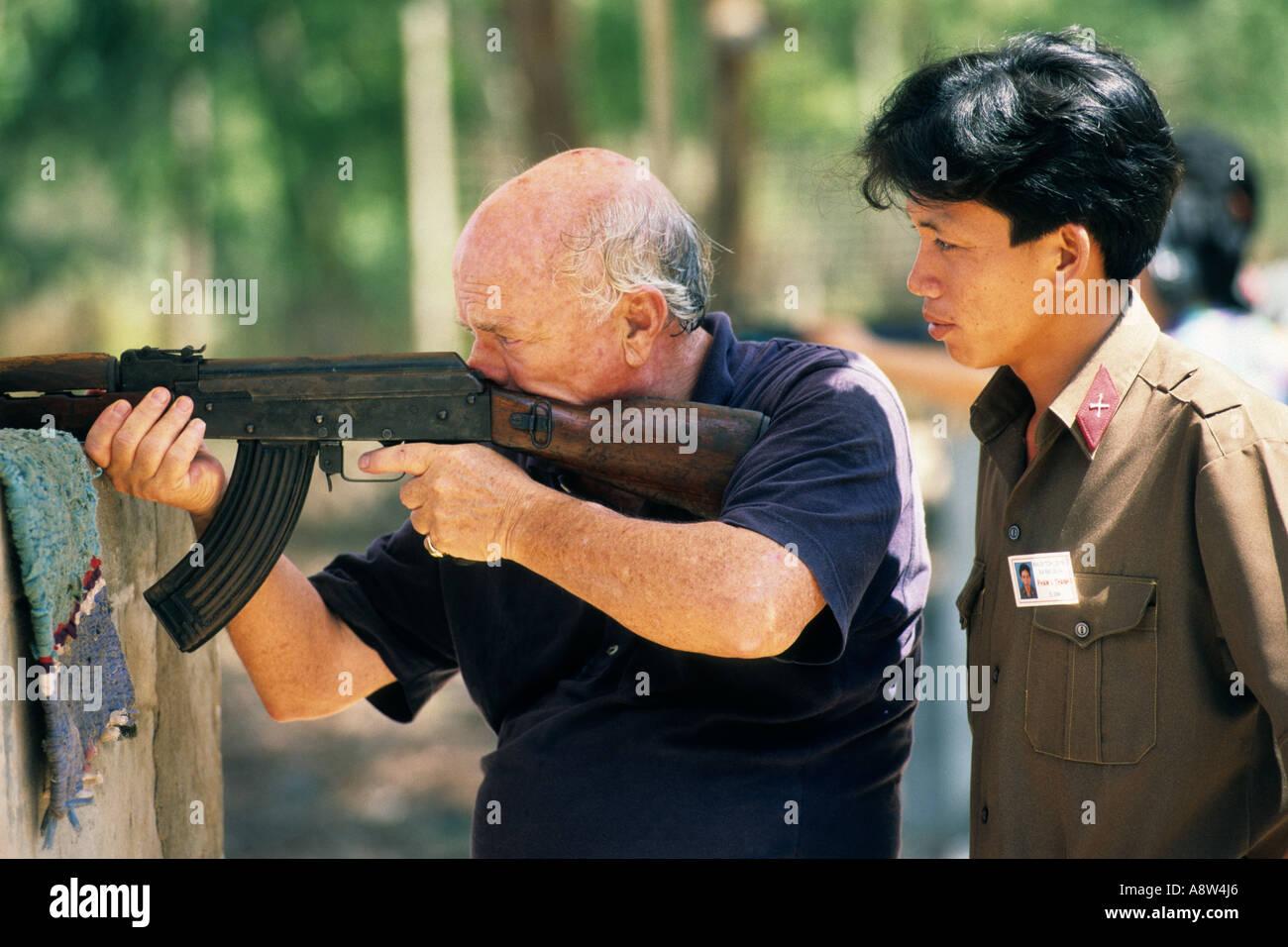 Asia, Vietnam, Cu Chi, ex veterano del Vietnam durante un esercizio di tiro su uno stand di tiro per turisti Immagini Stock