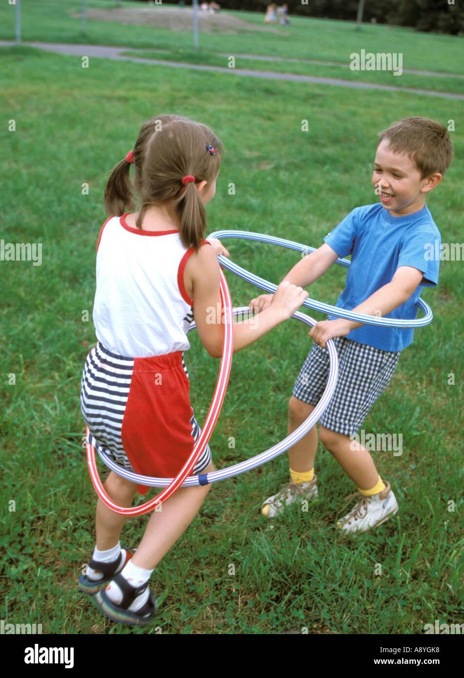 Un ragazzo e una ragazza a giocare con hula hop cerchi MR8417 7A Immagini Stock