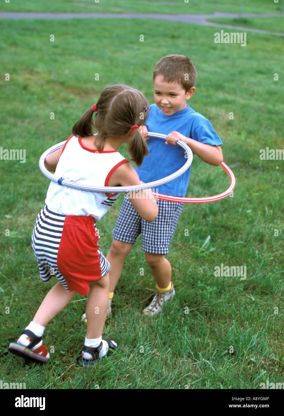 Un ragazzo e una ragazza a giocare con hula hop cerchio in park MR8417 7A Immagini Stock