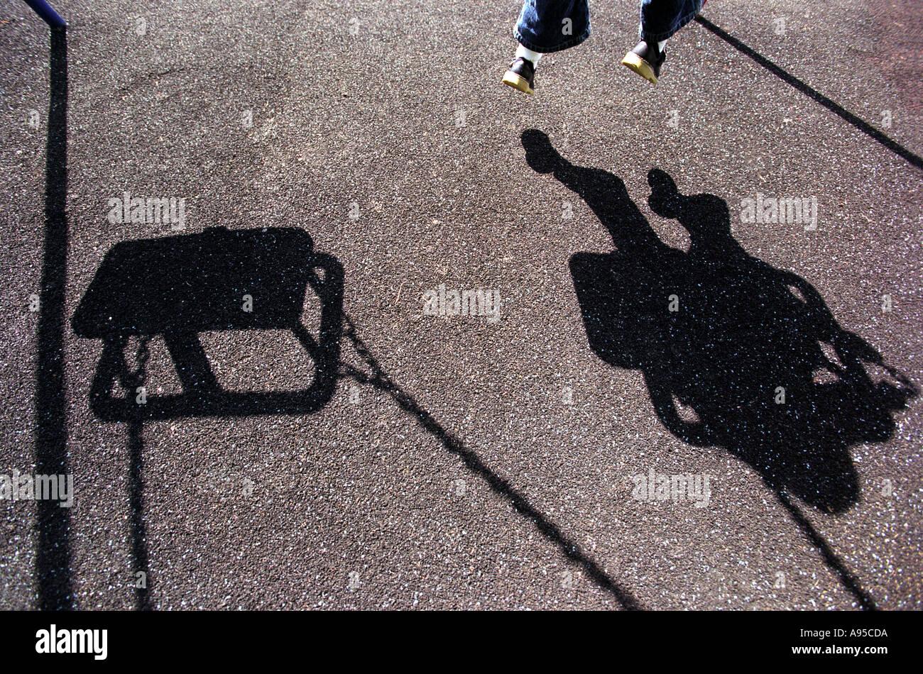 L ombra di una giovane ragazza o ragazzo giocando su uno swing Immagini Stock