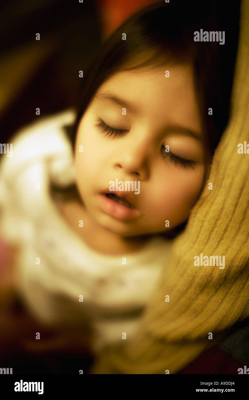 Testa e spalle ritratto di due anno vecchia ragazza dorme tra le braccia della mamma Immagini Stock