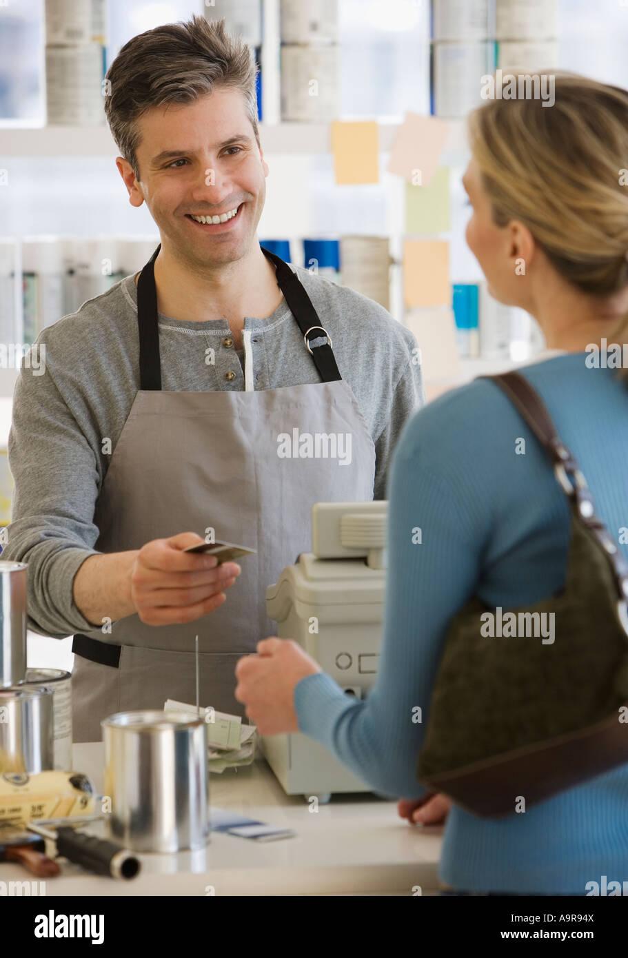 Donna pagando in negozio di vernice Immagini Stock
