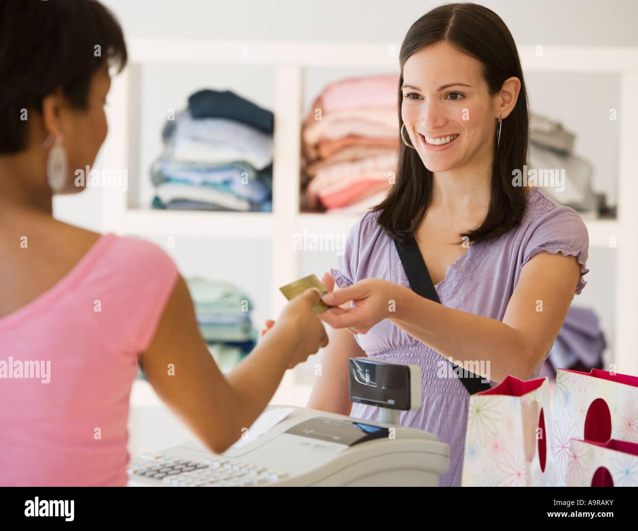 Donna pagando in negozio di abbigliamento Immagini Stock